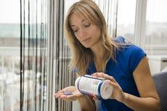 Mujer que toma una píldora Imágenes de archivo libres de regalías