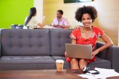 Mujer que toma una rotura que trabaja en Sofa In Design Studio Imagen de archivo
