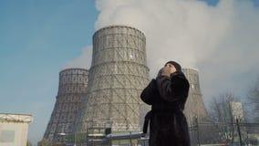 Mujer que tose cerca de las chimeneas de la fábrica almacen de metraje de vídeo