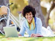 Mujer que trabaja al aire libre en un prado con el ordenador portátil Fotografía de archivo libre de regalías