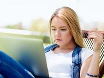 Mujer que trabaja al aire libre en un prado con el ordenador portátil Imagen de archivo
