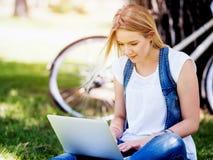 Mujer que trabaja al aire libre en un prado con el ordenador portátil Imágenes de archivo libres de regalías