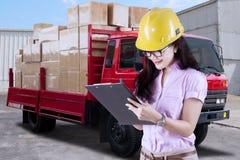 Mujer que trabaja con el camión de reparto en la fábrica imagen de archivo