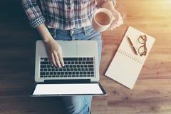 Mujer que trabaja con el ordenador portátil del cuaderno, usando el finger con el teclado para mecanografiar Ordenador port?til d fotos de archivo libres de regalías