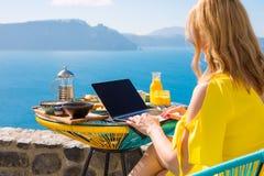 Mujer que trabaja con el ordenador portátil mientras que desayunando Fotografía de archivo