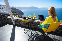 Mujer que trabaja con el ordenador portátil mientras que el vacaciones en mediterráneo Foto de archivo