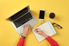 Mujer que trabaja con el ordenador port?til moderno y que escribe en cuaderno en la tabla de color fotos de archivo libres de regalías
