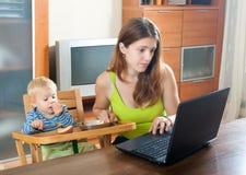 Mujer que trabaja con el ordenador portátil y el bebé Imagen de archivo