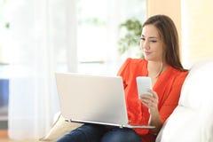 Mujer que trabaja con el ordenador portátil y el teléfono Imágenes de archivo libres de regalías