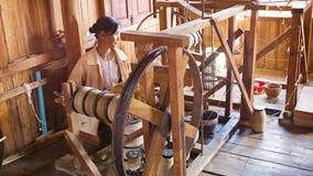 Mujer que trabaja con el viejo mecanismo para la producción de hilado almacen de metraje de vídeo