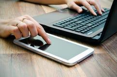 Mujer que trabaja con la tableta y el ordenador portátil Imagenes de archivo