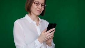 Mujer que trabaja con smartphone en fondo verde Llave de la croma Cierre para arriba metrajes