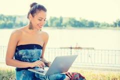 Mujer que trabaja con su ordenador portátil del cuaderno que se sienta en un césped imagen de archivo
