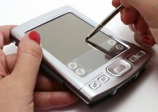 Mujer que trabaja con su palmtop Imágenes de archivo libres de regalías