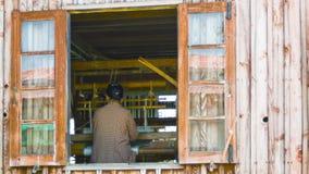 Mujer que trabaja con un telar La visión afuera a través de la ventana almacen de video