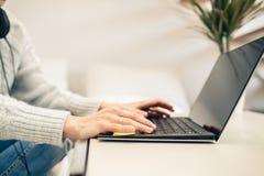 Mujer que trabaja de hogar en el ordenador portátil imagen de archivo