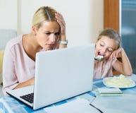 Mujer que trabaja de hogar, pequeña hija que pide la atención Imágenes de archivo libres de regalías