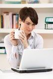 Mujer que trabaja de hogar usando la computadora portátil Imagenes de archivo