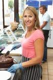 Mujer que trabaja detrás de contador en el café que rebana la torta Foto de archivo libre de regalías