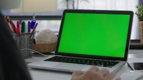 Mujer que trabaja en casa encendido con la pantalla del verde del ordenador port?til almacen de video