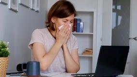 Mujer que trabaja en casa la oficina, sintiendo enferma y estornudando almacen de metraje de vídeo