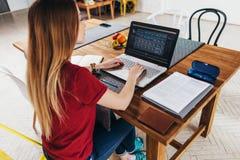 Mujer que trabaja en casa usando el ordenador portátil que se sienta en la tabla en la cocina, freelancer que trabaja en el cuade fotografía de archivo