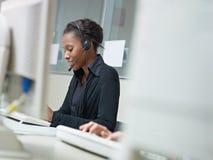 Mujer que trabaja en centro de atención telefónica Imagenes de archivo
