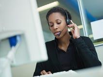 Mujer que trabaja en centro de atención telefónica Fotos de archivo libres de regalías