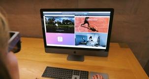 Mujer que trabaja en el último favorable puesto de trabajo profesional de Apple iMac almacen de video