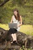 Mujer que trabaja en el ordenador en naturaleza Imagen de archivo