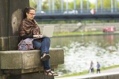 Mujer que trabaja en el ordenador portátil al aire libre en el sity Especialistas independientes Fotos de archivo libres de regalías