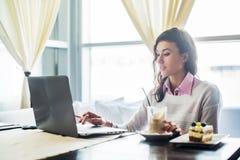 Mujer que trabaja en el ordenador portátil del ordenador portátil en el café, trabajo de la distancia de Internet, almuerzo de ne Fotos de archivo