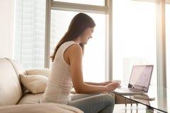 Mujer que trabaja en el ordenador portátil en apartamentos cómodos Imágenes de archivo libres de regalías