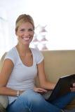 Mujer que trabaja en el ordenador portátil en casa Fotografía de archivo libre de regalías