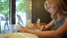 Mujer que trabaja en el ordenador portátil moderno en café metrajes