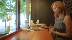 Mujer que trabaja en el ordenador portátil moderno en café almacen de metraje de vídeo