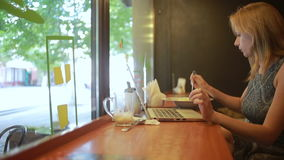 Mujer que trabaja en el ordenador portátil moderno en café almacen de video