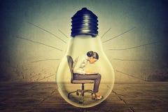 Mujer que trabaja en el ordenador portátil que se sienta dentro de bulbo de la luz eléctrica Fotos de archivo libres de regalías