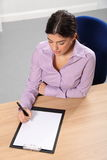 Mujer que trabaja en la escritura de la oficina en su escritorio Fotos de archivo