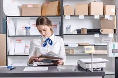 Mujer que trabaja en la oficina de correos Fotos de archivo libres de regalías