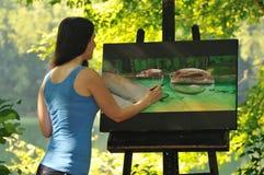 Mujer que trabaja en la pintura afuera foto de archivo