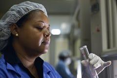 Mujer que trabaja en laboratorio pharamaceutical con los tubos de ensayo Foto de archivo libre de regalías