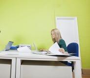 Mujer que trabaja en oficina contra la pared verde Foto de archivo libre de regalías