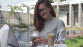 Mujer que trabaja en smartphone del ordenador portátil y de la toma cerca de piscina en el chalet de lujo tropical Trabajo femeni metrajes