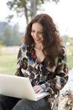 Mujer que trabaja en su computadora portátil en un parque. Imagen de archivo