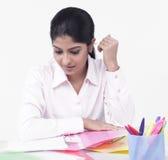 Mujer que trabaja en su escritorio de oficina Imagen de archivo libre de regalías