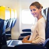 Mujer que trabaja en su ordenador portátil a bordo de un aeroplano foto de archivo