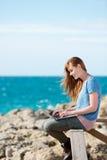 Mujer que trabaja en su ordenador portátil en la playa Imágenes de archivo libres de regalías