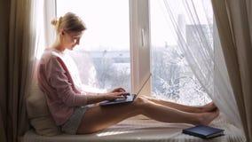 Mujer que trabaja en su ordenador portátil que se sienta en travesaño de la ventana Tiempo soleado del invierno almacen de metraje de vídeo