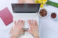 Mujer que trabaja en un cuaderno en cama Imagen de archivo libre de regalías